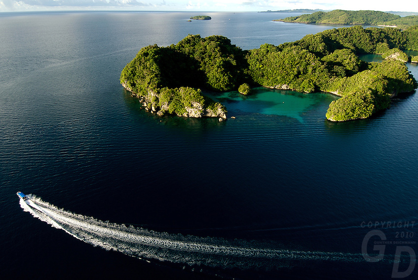 Aerial of the Rock Islands,Palau, Micronesia with Pinchers lagoon in the foreground and a dive boat cruising by