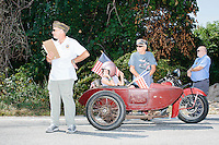 People in a vintage sidecar motorcycle prepare to ride in the Labor Day parade in Milford, New Hampshire. Republican candidates John Kasich, Carly Fiorina, and Lindsey Graham, and Democratic candidate Bernie Sanders marched in the parade.