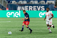 FOXBOROUGH, MA - OCTOBER 7: Scott Caldwell #6 of New England Revolution passes the ball as Ayo Akinola #20 of Toronto FC closes during a game between Toronto FC and New England Revolution at Gillette Stadium on October 7, 2020 in Foxborough, Massachusetts.