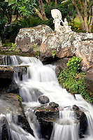 Peaceful waterfall with Asian statues overlooking falls