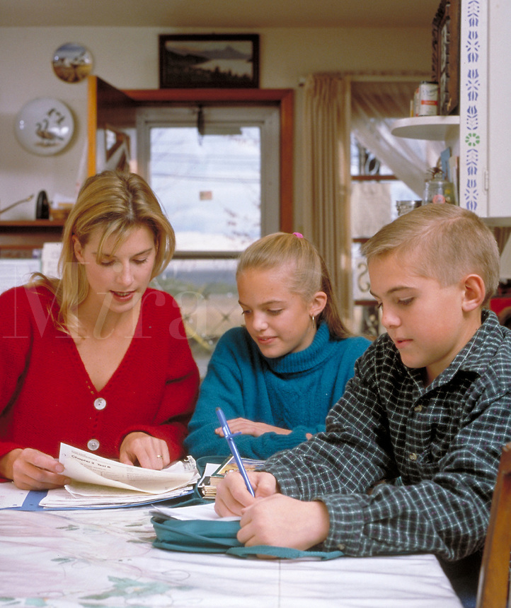 Mother and children at home at kitchen table doing homework together. mother, children, boy, girl, education, family activities, parent. B. Gehring & kids M.R.#K-9.