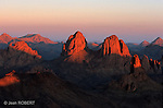 Saluer le lever du soleil est toujours un moment magique. Mais ici, au coeur du Sahara, perché à plus de 2700 mètres sur le plateau de l'Assekrem, l'apparition de l'astre solaire prend une dimension mystique. Les étoiles indifférentes au froid glacial résistent encore à l'aube naissante. L'horizon sort du mauve pour s'éclaircir peu à peu et vire du jaune à l'ocre. Le soleil se lève enfin sur les orgues basaltiques des Tezouyags (2702 m) et de la pointe Asaouinan (2337 m). La roche noire des pics déchiquetés encore enveloppés de nuit se réchauffe sous l'ardeur des premiers rayons du soleil. Comme le basalte  qui façonne ses paysages, le massif de l'Atakor se donne des airs de dureté pour mieux se révéler doux au toucher et friable au coeur.....The massif of the Atakor is the heart of Hoggar. The father De Foucault built a hermitage named Lassekrem. From this site perched 2700 m above sea level you can admire the sunset on basaltic peaks of Tezouyags. Hoggar, Algeria.