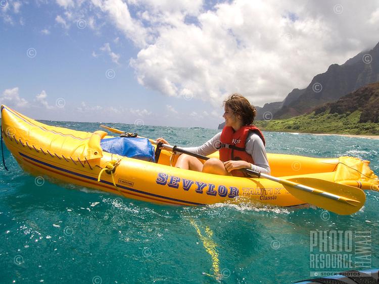 A young woman kayaks in a bright yellow Sevylor inflatable kayak off the coast of Kalalau Valley, Na Pali Coast, Kaua'i.