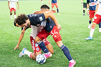 FOXBOROUGH, MA - JUNE 26: Ryan Spaulding #34 of the New England Revolution retrieves the ball from Alisson #27 of North Texas SC battling for it on the ground during a game between North Texas SC and New England Revolution II at Gillette Stadium on June 26, 2021 in Foxborough, Massachusetts.