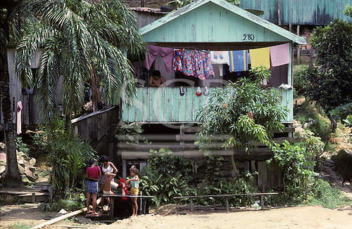 Manaus, Brazil. Timber stilt house in bright sunshine; family washing, washing hanging on a clothes line.