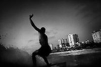 19 year old surfer Ali Ayrhim rides a wave in the Mediterranean Sea off Gaza City.
