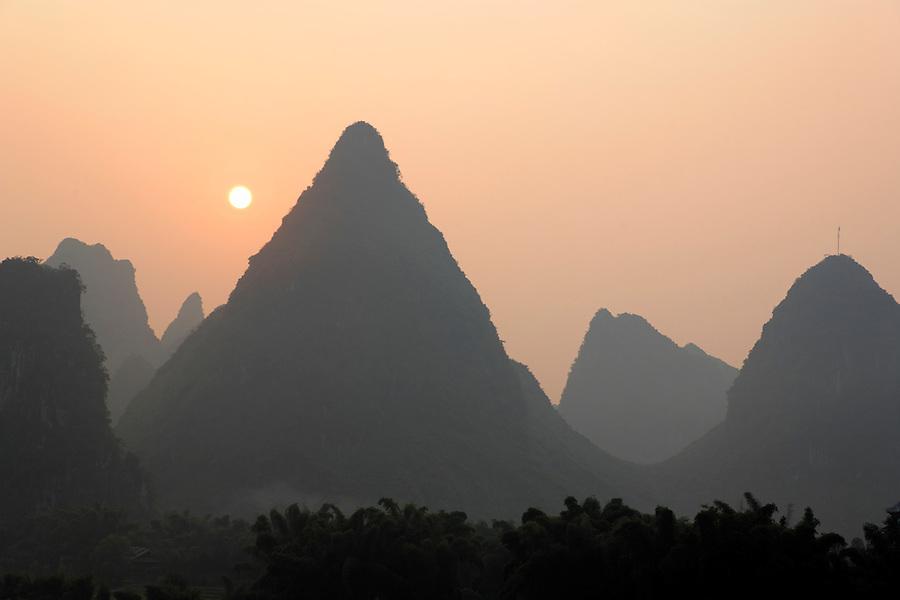 Sun rising over karst mountains, Yangshuo, Guanxi, China