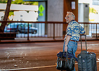 Older Caucasian man with luggage waiting for a ride at the Honolulu International Airport, O'ahu