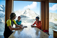Friends relax inside the Cabane de Moiry eating cake and drinking coffee during the  Via Valais, a multi-day trail running tour connecting Verbier with Zermatt, Switzerland.