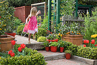 Young child, girl in pink dress jumping down steps leading into Rosalind Creasy front yard garden