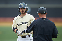 Patrick Frick (5) of the Wake Forest Demon Deacons bumps fists with first base coach Joey Hammond (29) during the game against the Notre Dame Fighting Irish at David F. Couch Ballpark on March 10, 2019 in  Winston-Salem, North Carolina. The Demon Deacons defeated the Fighting Irish 7-4 in game one of a double-header.  (Brian Westerholt/Four Seam Images)