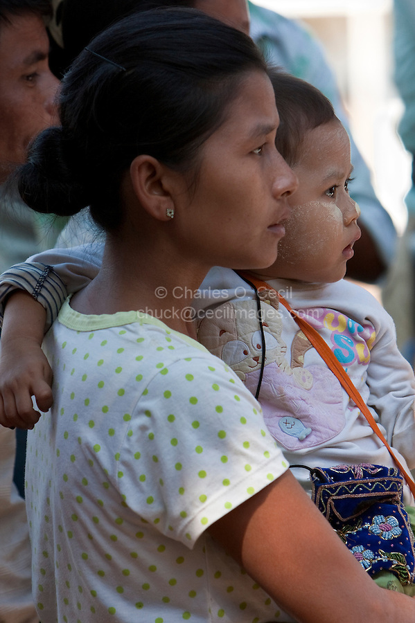 Myanmar, Burma.  Bagan.  Baby and Mother Watching Nat Pwe Dancers.  The baby has thanaka paste on his face, a protective sun-screen.