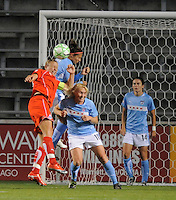 #20 Abby Wambach of the Washington Freedom tries to head a corner kick on goal against the defense of #10 Carli Lloyd and #18 Frida Osterberg of the  Chicago Red Stars . The Red Stars won the game 2-1