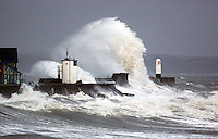 Pictured:  Huge waves crashing against the lighthouse wall in Porthcawl, south Wales. Friday 03 January 2014<br /> Re: Flood warnings have been issued  by the Environment Agency due to strong winds and high tides for part of the UK.