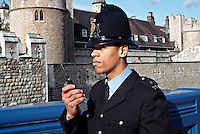 Police officer using his personal radio, on foot patrol in central London. The Tower of London can be seen in the background. This image may only be used to portray the subject in a positive manner..©shoutpictures.com..john@shoutpictures.com