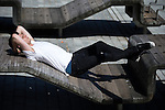 © Joel Goodman - 07973 332324 . 19/07/2016 . Manchester , UK . A man reclines on a bench in Ancoats . Sunshine in Manchester City Centre on the hottest day of the year so far . Photo credit : Joel Goodman