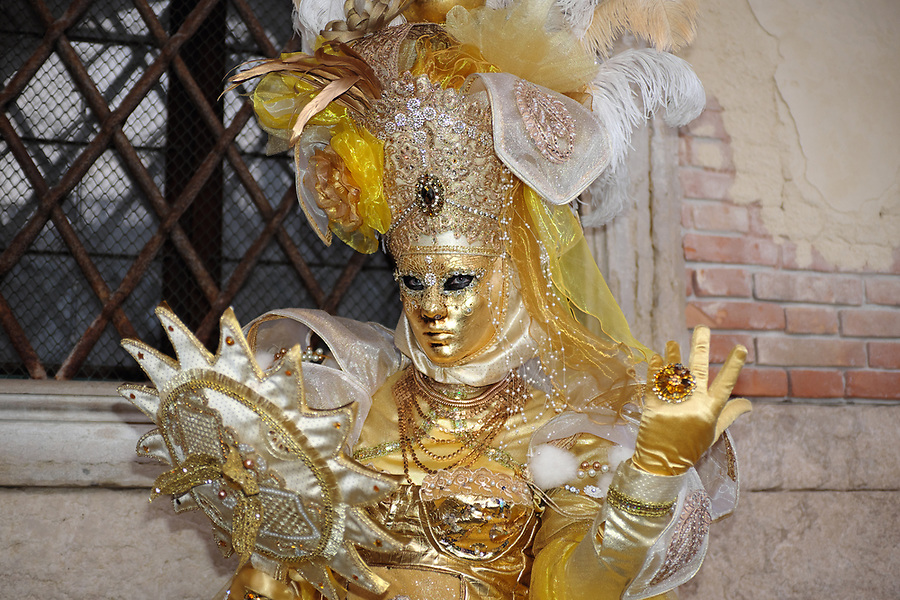 Woman dressed in traditional mask and costume for Venice Carnival looking into mirror standing at Doge's Palace, Piazza San Marco, Venice, Veneto, Italy