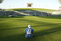 San Jose Earthquakes' Rodrigo Faria sits on an empty field at the Home Depot Center and calls his family in Brazil after the Earthquakes defeat the Chicago Fire 4-2 in the 2003 MLS Championship, in Carson, Calif.