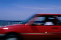 Red car speeding along the Corniche du Président J.F. Kennedy, Marseille, France.