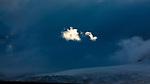 Antarctica, sunlit puff of cloud in dark, shadowy landscape