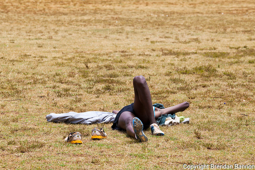 An athlete relaxing on the grass after running sprints at the track in Iten, Kenya.