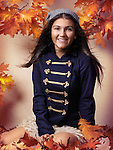Smiling teenage girl sitting on fallen autumn leaves artistic fall fashion portrait Image © MaximImages, License at https://www.maximimages.com