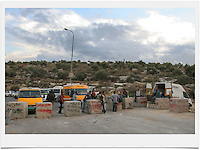 Palestinians gather at concrete blocks at the exit of the Palestinian village of Beit Sira to Road No. 443. Road 443 is one of the main throughways of the West Bank. Its overall length is 25.5 KM, 14 out of which run through the heart of the West Bank. .With the break of the second Intifada at the end of 2000, Israel had severely restricted Palestinian movement on road 443, which was their main road from the Beit Sira, Saffa, Beit Liqiya, Kharbatha al-Misbah, Beit Ur al-Tahata, Beit Ur al-Foqqa and al-Tira villages to Ramallah. These restrictions were harshened in 2002, when Palestinian movement was completely prohibited. In recent years all entries and exits from the road to the area's villages were blocked with gates and concrete slabs. Photo by Quique Kierszenbaum.