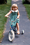 2 year old toddler girl riding tricycle on sidewalk full length no safety helmet