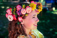 Girl as May fair princess with flower garland of roses in her hair