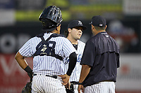 Pulaski Yankees relief pitcher Brett Morales (center) listens to pitching coach Gerardo Casadiego (55) during the game against the Princeton Rays at Calfee Park on July 14, 2018 in Pulaski, Virginia. The Rays defeated the Yankees 13-1.  (Brian Westerholt/Four Seam Images)