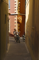 People ride bike on narrow street of Rethymno under bakery sign, Crete