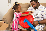 4 year old girl showing father something about directions for assembing plastic tricycle