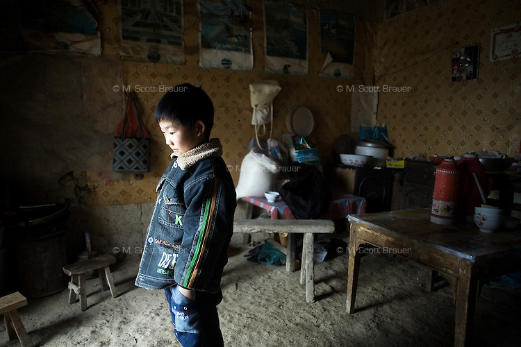Yan Jing Ya, 9, was orphaned and now lives with his grandparents in rural Yi Ling Village, Jiangsu Province, China.  The boy's father died in a coal mining accident; his mother, who had been purchased for a dowry for marriage from the remote Yunnan Province, remarried after the death and abandoned the child.  Yan Jing Ya's grandparents can not afford to care for the boy. ..Fan Wen Jie, 11, was orphaned in 2006 and now lives with his grandparents on a half hectare of land in rural Fanzhuan Village, Jiangsu Province, China.  The boy's father died in a car crash in 2005, and his mother remarried in 2006, abandoning the boy, though she still periodically sends money to help the family.  The boy's grandparents are frequently ill, and the meager income from farming cannot support his schooling.   ..At the time of the picture, China's Amity Foundation charity, was investigating the family's situation in preparation to raise money to financially support these children and other orphans in similar situations.  With Amity's support, each orphan, aged 6-12, would receive approximately 1,400 RMB annually (about 200 USD) to pay for the cost of living. Amity works to keep children out of the institutional orphanages in China, preferring to provide monetary assistance that can help maintain a family environment for the orphans it helps..