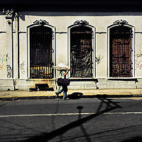 A Salvadoran street vendor walks in front of a unkept middle class house, designed by using bold Spanish colonial architecture elements, built in the center of San Salvador, El Salvador, 15 November 2016.