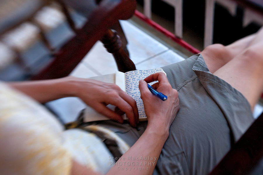 Young woman writing in journal on porch of hotel along city street, San Juan Del Sur, Nicaragua