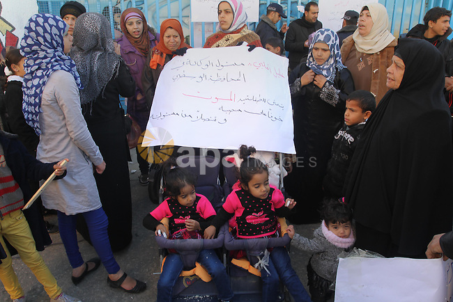 Palestinians take part in a protest in front of the headquarters of the United Nations (UNRWA) solidarity with the twins suffering from metabolic disorder, against the medical negligence for lack of early detection of their disease in Gaza City on December, 18, 2013. Photo by Mohammed Asad