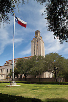 Texas flag flies with austin higher education tower in the background