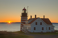 West Quoddy Head Light in Lubec, Maine as the sun rises over Grand Manan Island
