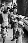 Mazatlan Mexico. Children busking in the crowded street, brother young sibling  playing a simple wooden percussion block and the youngest playing on a tin. Mexican music. Mexican state of Sinaloa 1973