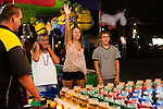 Lynn Burgarello, left, Jessica Burgarello and Sam Bachman try to win fish during the NV150 Fair at Fuji Park in Carson City, Nev., on Saturday, August 2, 2014.<br /> (Photo By Kevin Clifford)