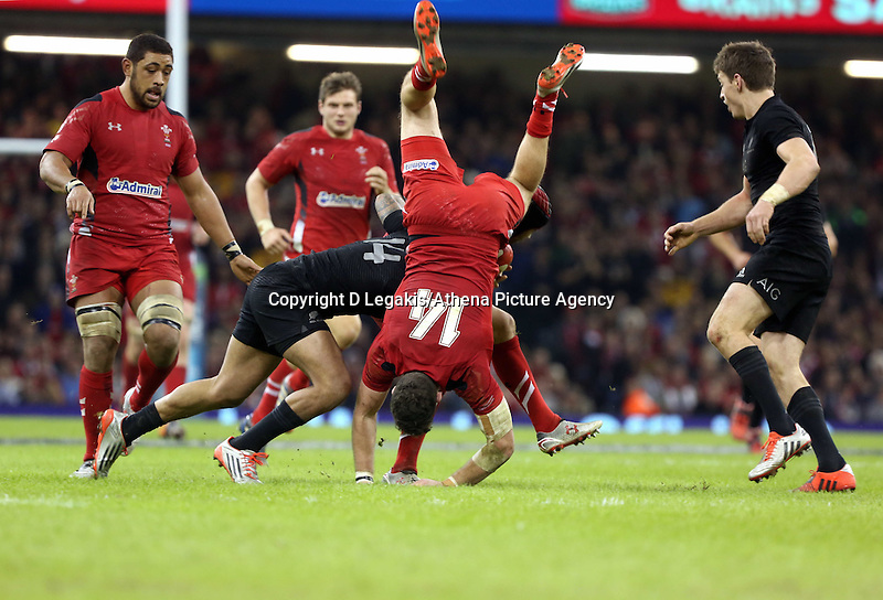 Pictured: Leigh Halfpenny of Wales (with ball) assisted by Cuthbert of Wales (TOP), is tackled by Charles Piutau of New Zealand, Alex  HSaturday 22 November 2014<br /> Re: Dove Men Series 2014 rugby, Wales v New Zealand at the Millennium Stadium, Cardiff, south Wales, UK.