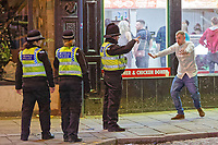 Pictured: A police officer speaks to a male reveller in Wind Street, Swansea. Monday 31 December 2018 and Tuesday 01 January 2019<br /> Re: New Year revellers in Wind Street, Swansea, Wales, UK