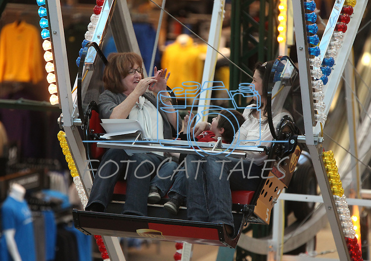 Nevada Sen. Debbie Smith, D-Sparks, takes a picture of Alexis Miller and her son, Cooper, 5, during the Scheels Ferris Wheel Dollar Challenge fundraiser for the Northern Nevada Children's Cancer Foundation on Friday, Feb. 1, 2013, at Scheels in Sparks, Nev. Cooper is fighting childhood leukemia. .Photo by Cathleen Allison