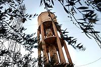 SYRIEN, 07.2014, Koreen (Provinz Idlib). Leben ohne Zentralregierung: Der Wasserturm, der mehrere Doerfer mit Trinkwasser versorgt, ist durch Beschuss schwer beschaedigt worden. Dank zahlloser Reparaturen funktioniert er aber und ist entscheidend fuer die Versorgung der Menschen - solange nicht die Pumpen ausfallen, was oefters der Fall ist. | Life without a central government: The water tower providing drinking water for several villages has been badly damaged by shelling. Thanks to countless repairs it is still in function and essential to the people's water supply - as long as the water pumps don´t break down which often is the case.<br /> © Timo Vogt/EST&OST