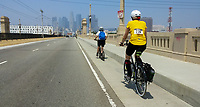 Holland kicks across the First Street Bridge on his Yedoo Dragstr kick scooter along with Michelle on her Terry Burlington city bike, with the Los Angeles skyline as a backdrop.  Taken during the 2017 (17th annual) Los Angeles River Ride.
