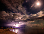 A lightning storm moves along the Forgotten Coast during a full moon at Shell Point in Waklulla County, Florida in the Florida panhandle.<br /> ©2013 Mark Wallheiser