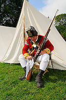 Lance Corporal of the Tenth Regiment of Foot cleans his short land pattern flintlock musket during a re-enactment of the 1775 Siege of Boston, Boston Common, USA.