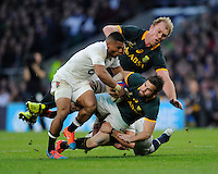 Cobus Reinach of South Africa is tackled by Anthony Watson and Tom Wood of England during the QBE International match between England and South Africa at Twickenham Stadium on Saturday 15th November 2014 (Photo by Rob Munro)