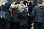 © Joel Goodman - 07973 332324 . 20/12/2017. Manchester, UK. A boy cries outside the church after the service . The funeral of 14-year-old Sam Berkley at Christ Church in Denton , East Manchester . Mourners wear red and white , the colours of Hattersley FC , for whom Berkley played . Amongst their number are pupils and friends from Audenshaw School . Berkley died after being hit by a grey BMW near junction 3 of the M67 in Hyde , East Manchester , on 1st December 2017 . Photo credit : Joel Goodman