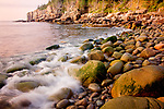 Waves splash a cobble beach in Acadia National Park, ME, USA